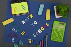 School set with blue paper, text & x22;Back to school& x22; of wooden letters, calculator, markers and other stationery. School set with blue paper, text Stock Image