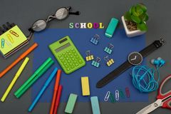 School set with blue paper, text & x22;School& x22; of wooden letters, calculator, markers, eyeglasses, watch and other stationery. On grey background royalty free stock photo