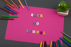 School set with pink paper, text & x22;Back to school& x22; of wooden letters and crayons. School set with pink paper, text & x22;Back to school& x22; of Royalty Free Stock Image