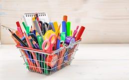 School shopping basket on white background. School supplies in a shopping basket on white background Royalty Free Stock Image