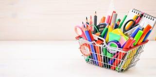 School shopping basket on white background. School supplies in a shopping basket on white background Royalty Free Stock Photo