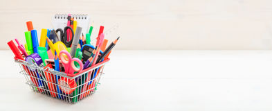 School shopping basket on white background. School supplies in a shopping basket on white background Royalty Free Stock Images