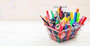 School shopping basket on white background. School supplies in a shopping basket on white background Stock Images