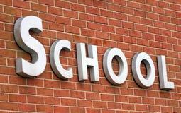 School Sign. The word school on brick wall Stock Image