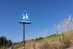 School Sign, children crossing sign beside the street with clear. Blue sky in autumn Japan Stock Photography