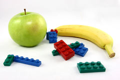 After School Snack. A fresh Granny Smith apple and a ripe banana photographed on a white background with an assortment of colorful plastic building blocks Royalty Free Stock Photography