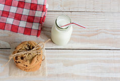 After School Snack. High angle shot of an after school snack of chocolate chip cookies and an old fashioned bottle of milk. The cookies are tied with twine and Stock Image