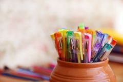 School stationery on a colored background. In a clay pot Stock Photos