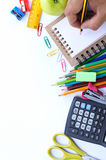 School stationery and human hand writing on small notebook on white background. Back to school concept Stock Photos