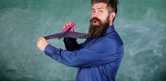 School stationery. Man scruffy use stapler dangerous way. Hipster teacher formal wear necktie holds stapler. Teacher. Bearded man with pink stapler chalkboard stock images