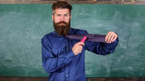 School stationery. Man scruffy use stapler dangerous way. Teacher bearded man with pink stapler chalkboard background. School accident prevention. Hipster stock image