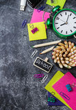 School stationery, pencil, pen, note, alarm clock on grunge chalkboard Royalty Free Stock Image