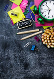 School stationery, pencil, pen, note, alarm clock on grunge chalkboard Stock Photos