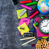 School stationery, pencil, pen, note, alarm clock on grunge chalkboard Royalty Free Stock Photography