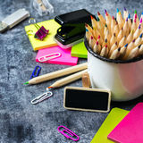 School stationery, pencil, pen, note, alarm clock on grunge chalkboard Stock Images