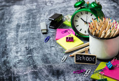 School stationery, pencil, pen, note, alarm clock on grunge chalkboard Royalty Free Stock Photo