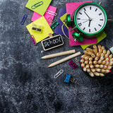 School stationery, pencil, pen, note, alarm clock on grunge chalkboard Royalty Free Stock Photos