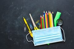 Free School Stationery Supplies, Medical Masks On The Blackboard. Back To School After Covid-19 Coronavirus.Concept Of Learning, Royalty Free Stock Photography - 189706867