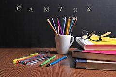 Back to school. School Stationery  are on the table infront of a black board Stock Photos