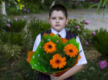 The school student with a beautiful bouquet of flowers, the front view. A subject on September 1, the beginning of occupations, the end of occupations Stock Image