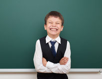 School student boy posing at the clean blackboard, grimacing and emotions, dressed in a black suit, education concept, studio phot Stock Photos