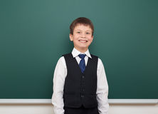School student boy posing at the clean blackboard, grimacing and emotions, dressed in a black suit, education concept, studio phot Royalty Free Stock Photos