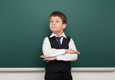 School student boy posing at the clean blackboard, grimacing and emotions, dressed in a black suit, education concept, studio phot Royalty Free Stock Images