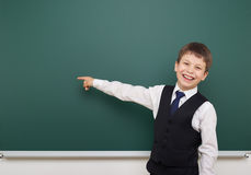 School student boy posing at the clean blackboard, show finger and point at, grimacing and emotions, dressed in a black suit, educ Stock Photo