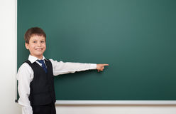 School student boy posing at the clean blackboard, show finger and point at, grimacing and emotions, dressed in a black suit, educ Stock Image