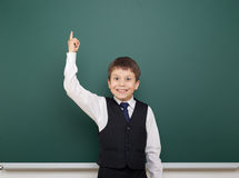 School student boy posing at the clean blackboard, show finger up and point, grimacing and emotions, dressed in a black suit, educ Stock Photo