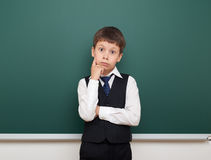 School student boy posing and think at the clean blackboard, grimacing and emotions, dressed in a black suit, education concept, s Royalty Free Stock Photo