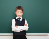 School student boy posing and think at the clean blackboard, grimacing and emotions, dressed in a black suit, education concept, s Stock Image