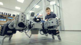 School student controls self-made robot at engineering school lab.