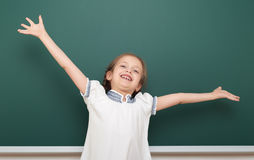 School student girl open arms at the clean blackboard, grimacing and emotions, dressed in a black suit, education concept, studio Royalty Free Stock Photography