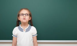 School student girl posing at the clean blackboard, grimacing and emotions, dressed in a black suit, education concept, studio pho Royalty Free Stock Photo