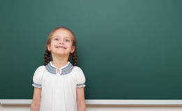 School student girl posing at the clean blackboard, grimacing and emotions, dressed in a black suit, education concept, studio pho Royalty Free Stock Images