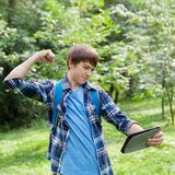 School student holding tablet. Anger, aggression school student holding tablet, walk in summer park, outdoor, teen Royalty Free Stock Photos