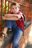 School student sitting. Child sitting on the edge of a brick and wrought iron wall with school bag slung over shoulder. Browse more of my Kids Pics stock photography