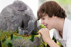 School student working on model building project. Teenager working on model building school project. Kids build miniature scale model mountain for geography Stock Photo