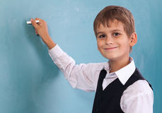 School student writing on blackboard at school Royalty Free Stock Photo