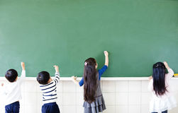 School students drawing on chalkboard. Rear view of school students drawing on chalkboard Stock Image