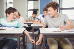School students passing a chit in a secretive way inside the classroom. At school stock photography