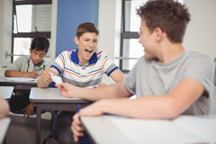School students passing a chit in a secretive way inside the classroom. At school royalty free stock photo