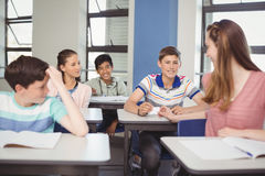 School students passing a chit in a secretive way inside the classroom. At school royalty free stock photography