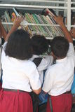 School students reading a book in the mobile library Royalty Free Stock Images