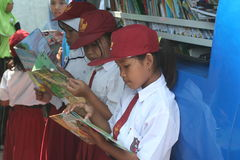 School students reading a book in the mobile library Royalty Free Stock Photo