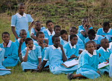 School students sit on the earth and wait for the school bus. Stock Images