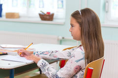 At school, the students sit in the pew: Portrait.  Royalty Free Stock Images