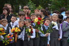 School students stand with flowers in hands on September 1. Stock Images