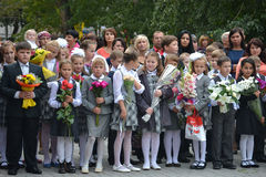 School students stand with flowers in hands on September 1. Stock Image